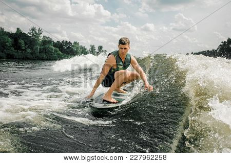 Young Brunette Caucasian Man Riding Stylish Wakeboard On High Wave Of Motorboat, Spiting Out Spray
