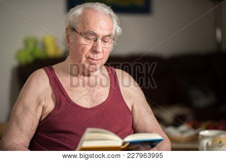 Old Man Reading A Book In His House