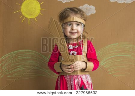Portrait Of A Playful Child With A Cardboard Sword And A Suit. Vintage Style