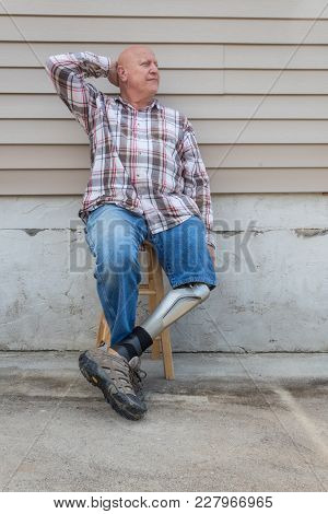 Amputee Man Sitting On Stool With Prosthetic Leg Crossed, Had Behind Head, Copy Space, Vertical Aspe