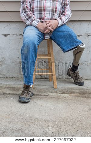 Leg Amputee Sitting On Stool With Prosthetic Leg To The Side, Copy Space, Vertical Aspect