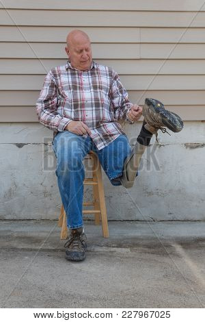 Seated Amputee Man Holding Rotated Prosthetic Leg Up By Shoe Loop, Copy Space, Vertical Aspect