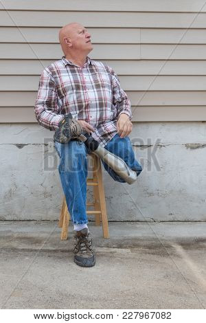 Smiling Amputee Man Sitting On A Stool, Prosthetic Leg Crossed, Looking Up, Copy Space, Vertical Asp