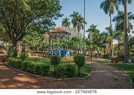 Old Colorful Gazebo In The Middle Of Square And Verdant Garden Full Of Trees, At Sunset In Sao Manue