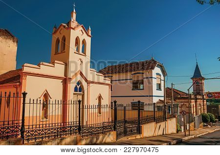 Sao Manuel, Southeast Brazil - October 14, 2017. Facade Of Small Church And Belfry Behind Iron Fence