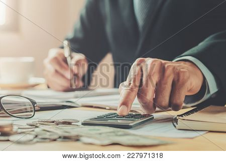 Accountant Using Calculator To Calculate Of Money Budget On Desk In Office. Business Finance And Acc