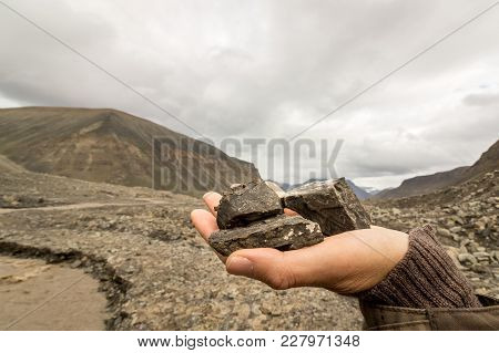 Female Hand Holding Coal Found By The Longyear Glacier. Brown Meltwater River And Arctic Landscape O