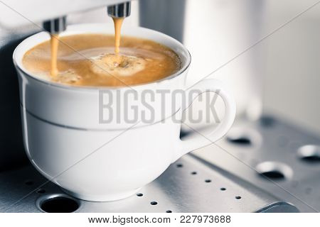 Closeup Of Creamy Coffee Dripping From Machine Into Coffee Cup