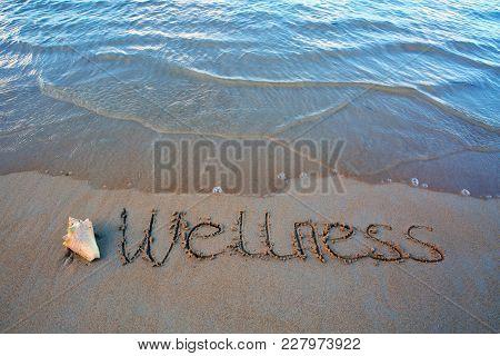 Word Wellness Written On The Sand Near The Sea. Wellness Concept Written On Sand.
