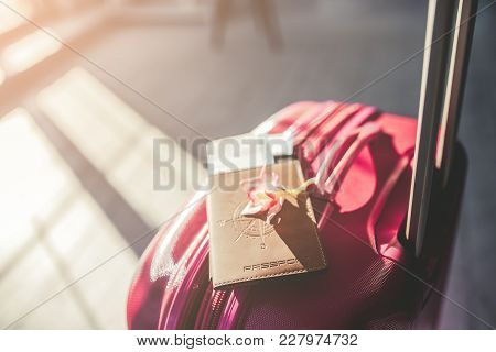 Cropped Image Of Pink Suitcase Is Standing In Light Sunny Room With Passport, Ticket And Exotic Flow
