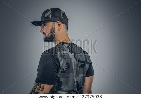 Stylish Bearded Male In A Cap From The Back Isolated On Grey Background.