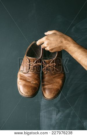 Old Man's Brown Shoes In Hands On A Dark Background. Casual Style