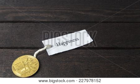 Backside Of Bitcoin And The Word: Happiness On Wooden Background