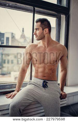 Shirtless Muscular Man With Beard Posing Near Window.