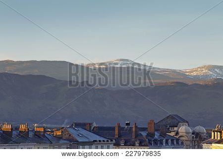 Scenic Hills Of Snowdonia Dusted In Snow Above Roof Tops Of Victorian Building. Llandudno, North Wal