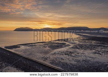 Raising Sune Over Northern Shore Of Llandudno At Low Tide. North Wales, Uk
