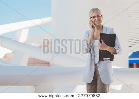 Young Blond Businesswoman Posing In A Modern Building Talking On The Phone.