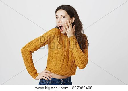 Surprised And Intrigued Attractive Young Woman Holding Hands On Waist And Cheek, Being Half-turned A