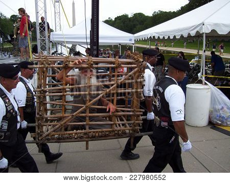 Individual Being Carried In A Wooden Cage At An Mia And Pow Event In Front Of The Lincoln Monument,