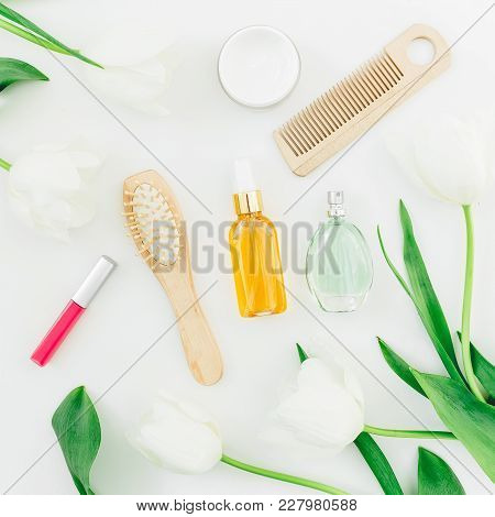 Cosmetics, Perfume, Hair Styling Tools And Tulips Flowers On White Background. Beauty Blog Compositi