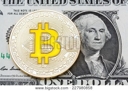 Golden Bitcoin Coin On Us Dollars Close Up. High Resolution Photo.