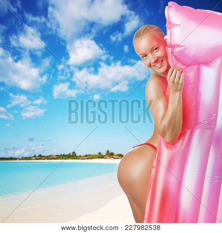 Sexual Blond Female Posing With A Pink Water Matress. Isolated On A White Background.