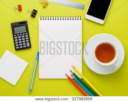 Top View Of Modern Bright Yellow Office Desktop With Blank Notepad, Cup Of Tea And Supplies. Mock Up