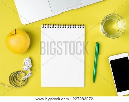 Blank Notebook Page For Diet Plan Or Menu, Tape Measure, Water In Glass And Apple On Bright Yellow B