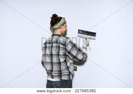 Diligent Young Woman In A Plaid Shirt Leveling A Wall With A Spatula, Repairing