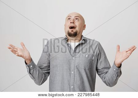 Portrait Of An Adult Man Looking Up In The Sky With Surprised Or Shocked Expression Over White Backg