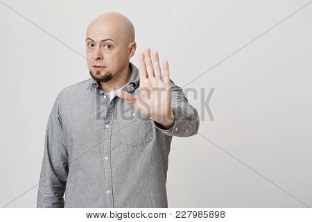Serious Confident Angry European Bald Man With Beard Wearing Stylish Gray Shirt Posing Against Gray