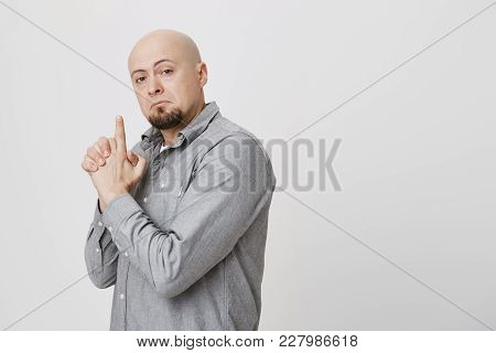 Confident Bald Businessman In Gray Shirt Makes Shooting Gesture, Ready To Reach Great Success. Good