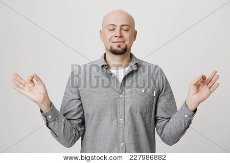Yoga And Meditation. Bald Man With Beard Dressed In Shirt Keeping Eyes Closed While Meditating, Feel