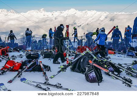 Skiers And Snowboarders With Their Gear With Stunning View Of Valley Below At Ski Resort In Valle D'