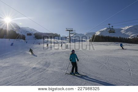 Skiers At Ski Resort In Pila, Valle D'aosta, Italy With Chairlift And Mountain Backdrop And Copy Spa