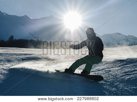 Young Snowboarder Shooting Into The Sun - Winter Sports Concept