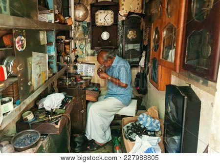 Kandy, Sri Lanka - Jan 6, 2018: Elderly Watchmaker Works In The Workshop With Vintage Watches Around