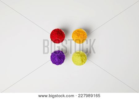 Top View Of Four Colors Of Holi Powder In Bowls On White, Hindu Spring Festival