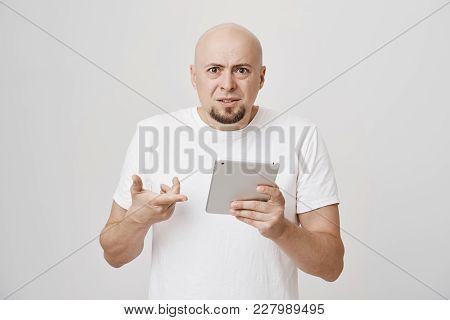 Indoor Portrait Of Irritated Upset Bald Caucasian Male Holding Tablet And Pointing At It, While Frow