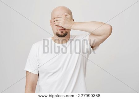Studio Portrait Of Calm Bald Bearded Caucasian Guy Covering Eyes With Hand, Wearing White T-shirt An