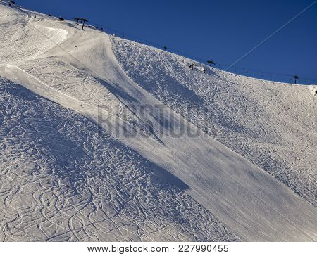 Steep Gradient Piste In Italian Alps With Lone Expert Snowboarder Heading Down, Against A Beautiful