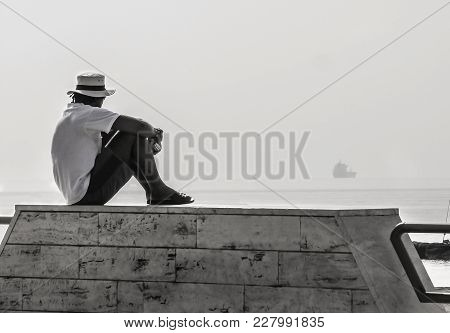 One Man Sits On A Promenade Of Naples And Looks Far At The Sea. There Is A Single Ship Sails Over Th