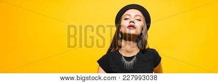 Attractive Luxury Young Girl In A Black Hat Posing, In The Ears Expensive Earrings