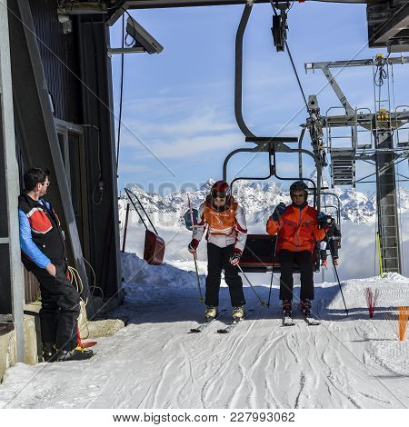 Older Man And Teenager Get Off Chairlift At Ski Resort With Majestic Italian Alps In Background