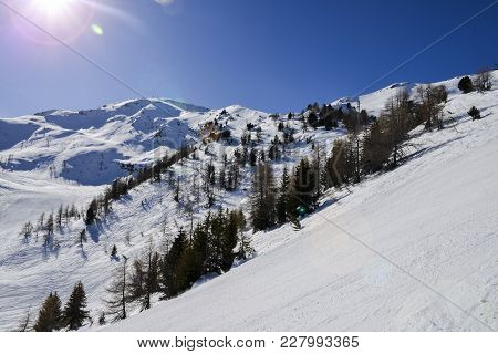 Steep Gradient Piste In Italian Alps, Against A Beautiful Blue Sky And Sun Flares