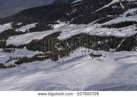 Unidentifiable Skiers At Ski Resort In Pila, Valle D'aosta, Italy With Chairlift And Mountain Backdr