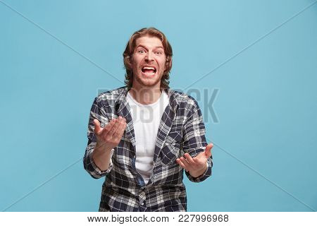 Argue, Arguing Concept. Beautiful Male Half-length Portrait Isolated On Blue Studio Backgroud. Young