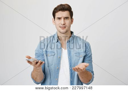 Portrait Of Attractive Young Adult With Perplexed And Confused Expression, Holding Smartphone And Sh