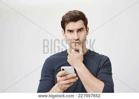 Indoor Shot Of Young Caucasian Student Looking Worried And Perplexed While Holding Smartphone And To