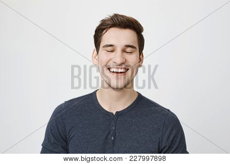 Pleased Delightful Smiling Dark-haired Male With Stubble And Closed Eyes Has Dreamy Expression, Wear
